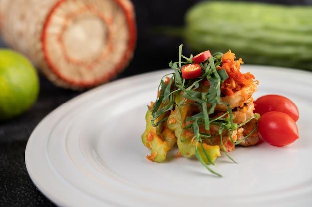 Острый салат из свинины с лаймом с горькой дыней, галангал, чили, помидорами и чесноком в белой тарелке на черном цементном полу.