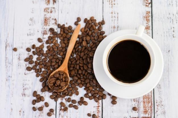Кофейная чашка и кофейные зерна в деревянной ложке на белой таблице.