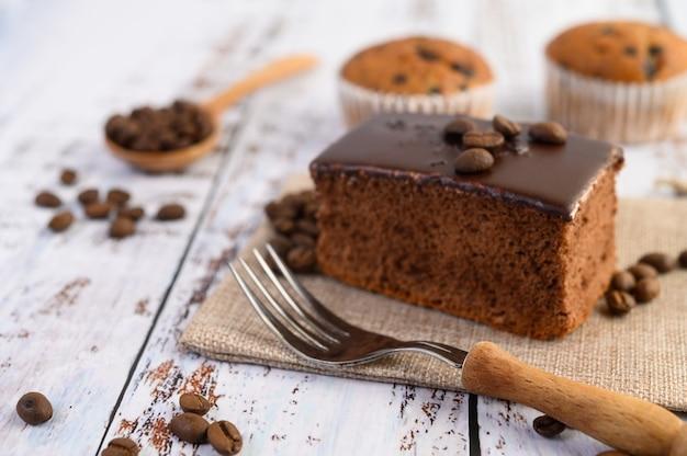Шоколадный торт на мешок и кофейных зерен с вилкой на деревянном столе.