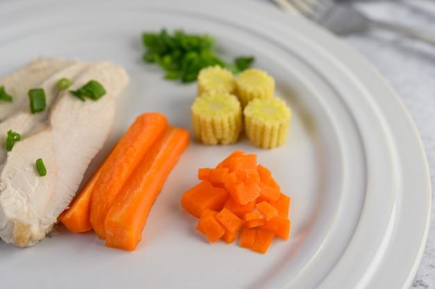 Паровая куриная грудка на белой тарелке с зеленым луком, кукурузой и нарезанной морковью.