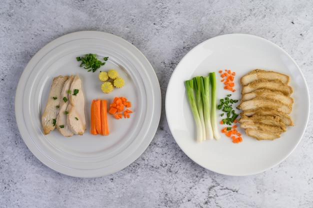Паровая куриная грудка на белой тарелке с зеленым луком и нарезанной морковью