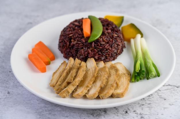 カボチャ、エンドウ豆、ニンジン、ベビーコーン、蒸し鶏の胸肉のプレートに黒ご飯。