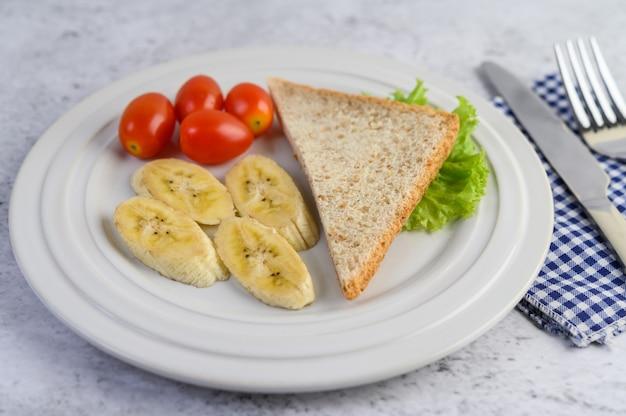 フォークとナイフで白い皿にパン、バナナ、トマト。