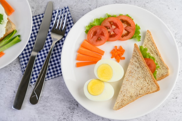 ゆで卵、パン、ニンジン、トマトを白い皿にナイフとフォークで。