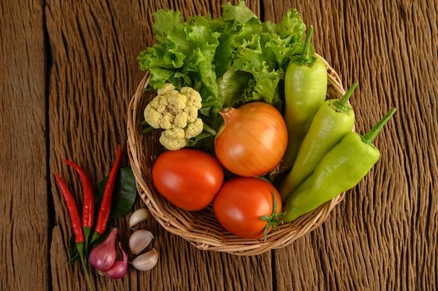 ピーマン、トマト、タマネギ、サラダ、唐辛子、エシャロット、ニンニク、カリフラワー、カフィアライムの葉、木製のテーブルの木製バスケット