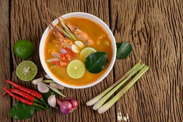 トムヤムクンタイホットスパイシーなスープエビとレモングラス、レモン、ガランガル、唐辛子、木製のテーブル、タイ料理