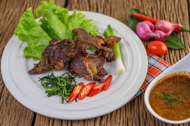 ネギ、カフィアライムの葉、唐辛子、サラダ、赤玉ねぎ、トマトの白い皿に牛肉のフライ揚げタイ料理。
