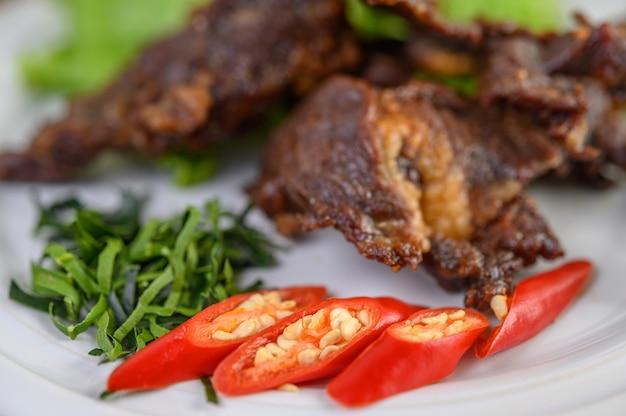 ネギ、カフィアライムの葉、唐辛子、サラダ、チリペーストをカップに入れて白い皿にビーフフライで揚げたタイ料理。