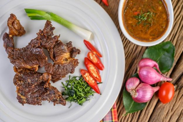 ネギ、ライムの葉、唐辛子、赤玉ねぎ、トマトの白い皿に牛肉のフライ揚げタイ料理。