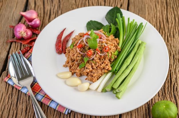 レンズ豆、カフィアライムの葉、ネギの白い皿にスパイシーなミンチポークサラダ。