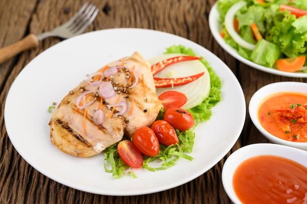 Жареная курица на белой тарелке с помидорами, салатом, луком, чили и соусом.