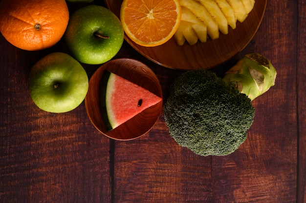スイカ、パイナップル、オレンジ、アボカド、ブロッコリー、リンゴを木のテーブルにカットします。上面図。
