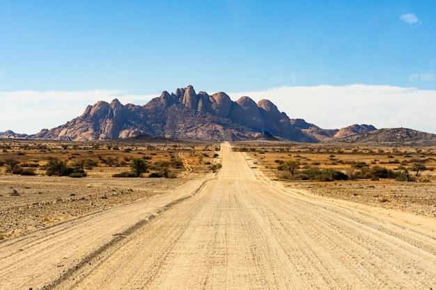 Дорога в горы шпицкоппе. шпицкоппе, группа пиков лысого гранита, расположенная в пустыне свакопмунд намиб - намибия