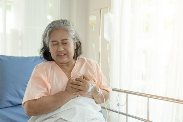 自宅で胸部心臓発作のひどい痛みに苦しんでいるアジアのシニア女性-シニア心臓病