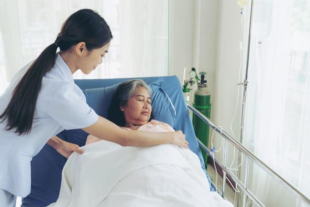 看護師は病院のベッドの患者の高齢の女性患者の世話をよくされている幸せを感じる-医療とヘルスケアの概念