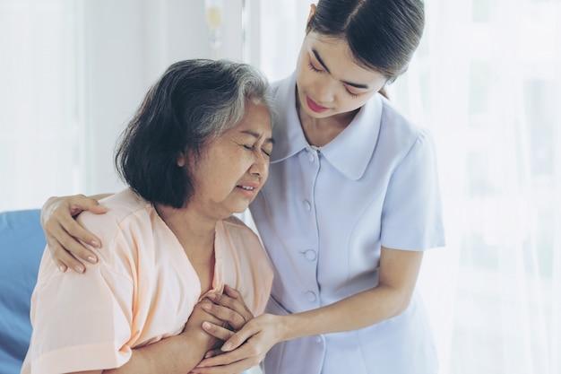 看護師は病院のベッドの患者の高齢の女性患者の世話をします