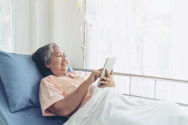 Пожилые пожилые пациенты в больничной койке, использующие умный телефонный звонок, чтобы родственники-потомки чувствовали счастье - старшая женская медицинская и медицинская концепция