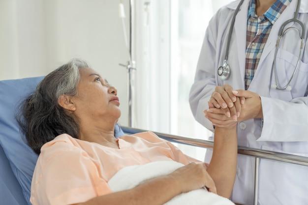 医師は病院-シニア女性の医療とヘルスケアの概念で高齢者のシニア女性患者を奨励するために手を握る