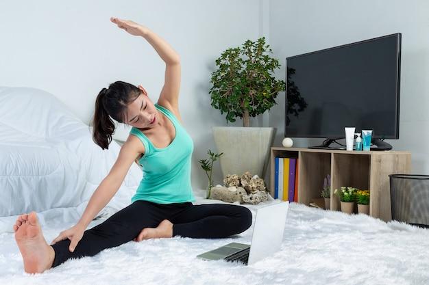 Молодая девушка работает дома, она практикует йогу дома. концепция здорового образа жизни от вируса.