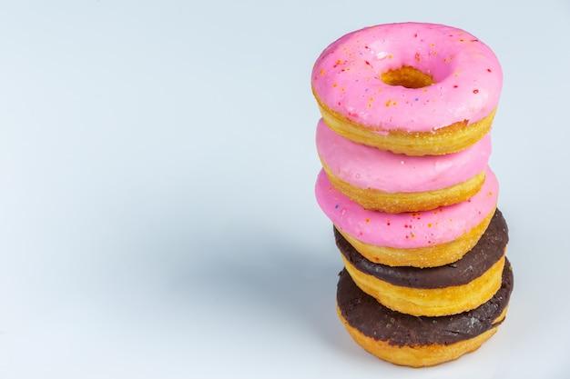 色の壁にピンクの積層チョコレート釉薬ドーナツ。