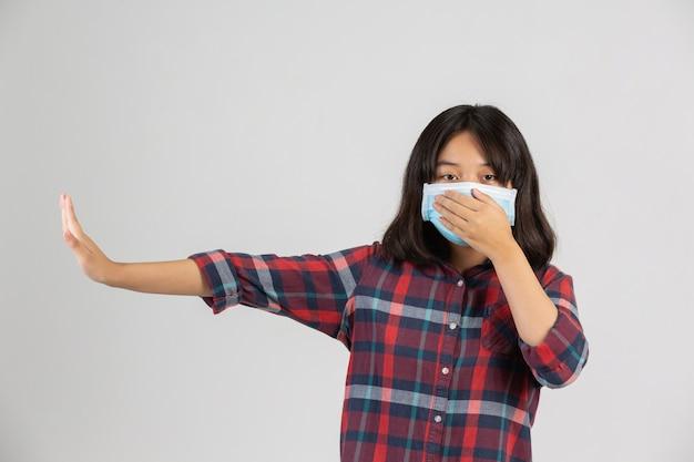 かわいい女の子はマスクをしていて、白い壁に他のプロパティからストップハンドを作っています。