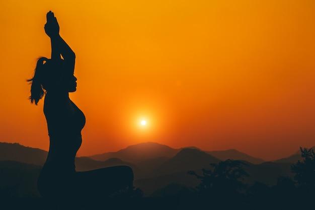シルエット-日没時に屋上でヨガの女の子が練習しています。