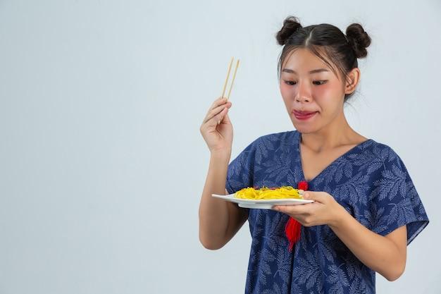 若い女の子は自宅でスパゲッティを食べることを楽しむ