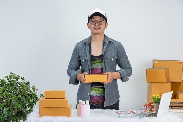 ビジネスの男性が壁にホームオフィスのパッケージで顧客のためにオンラインで作業しています