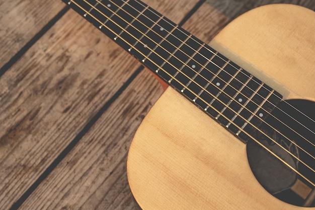 Акустическая гитара на деревянной стене .. винтажная гитара