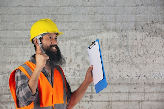 Рабочий-строитель с документом, планом работая для внутренней строительной площадки здания.