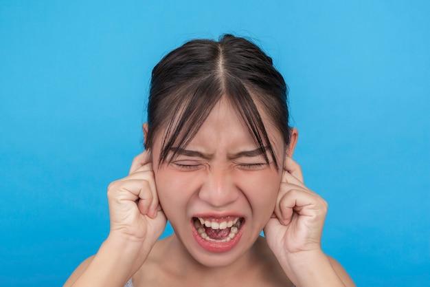 Молодая девушка несчастна и пытается закрыть уши руками на голубой стене.
