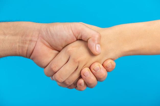 Рукопожатие между молодой мальчик и молодая девушка на синей стене.