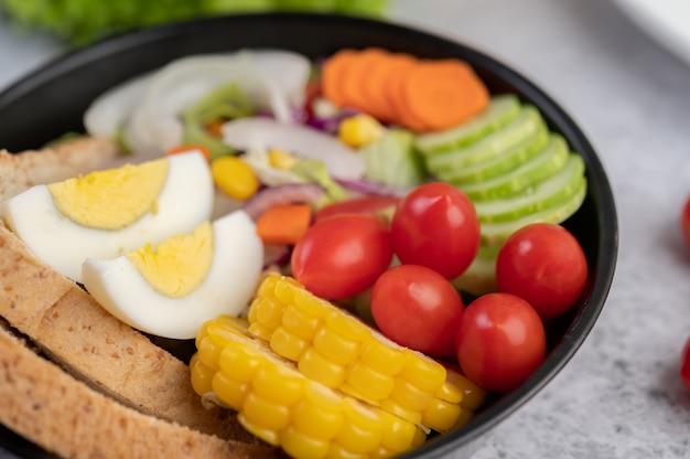 パンとゆで卵を鍋に入れた野菜サラダ。