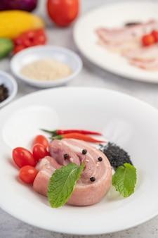 コショウの種のトマトとスパイスが入った白い皿に豚バラ肉。
