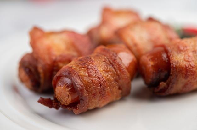 Обернутая сосиска свиная грудинка на белой тарелке.