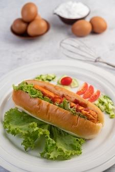 パンとレタスにソースをかけたソーセージ。