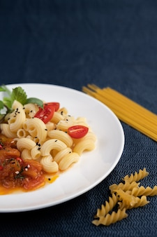 Жареные макароны с помидорами, перцем чили, перцем и базиликом в белом блюде.