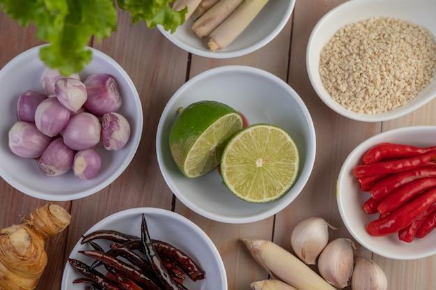 Красный лук, лимон, лемонграсс, перец чили, чеснок, галангал и салат в чашке на деревянном полу.