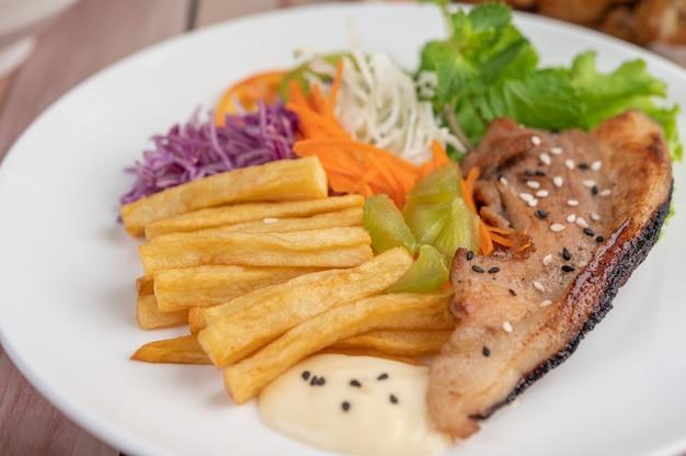 Стейк из рыбы с картофелем фри, киви, листьями салата, морковью, помидорами и капустой в белом блюде.