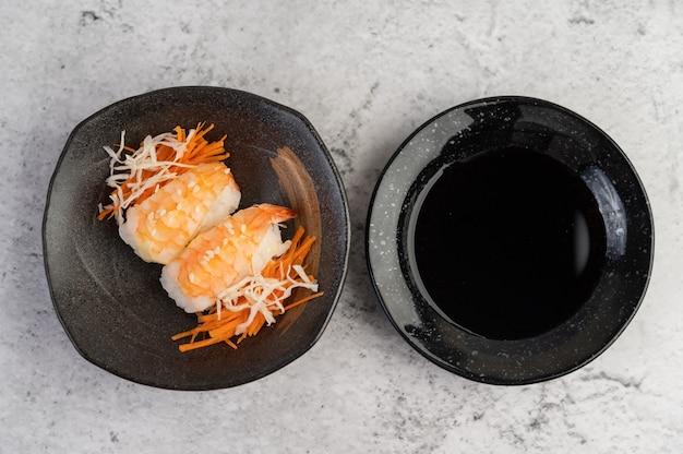 寿司は白いセメントの床にディップソースが付いた皿の上にあります。