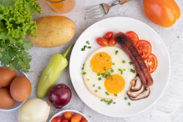 Завтрак, состоящий из хлеба, яичницы, помидоров, китайской колбасы и грибов.