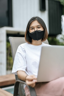 マスクをしてプールサイドでラップトップをする女性。