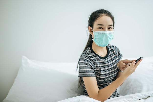 Девушка в маске и полосатой рубашке играет на смартфоне.
