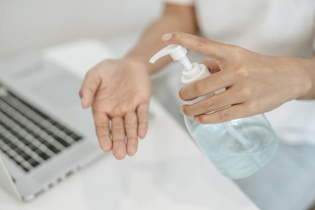 ジェルを押して手を洗う白いシャツを着ている女性。