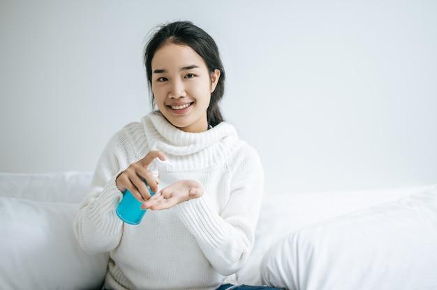 若い女性は手洗いジェルで手を洗います。