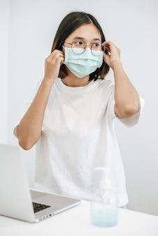 生理用マスクを身に着けている女性は、テーブルと手洗いジェルの上にラップトップを持っています。
