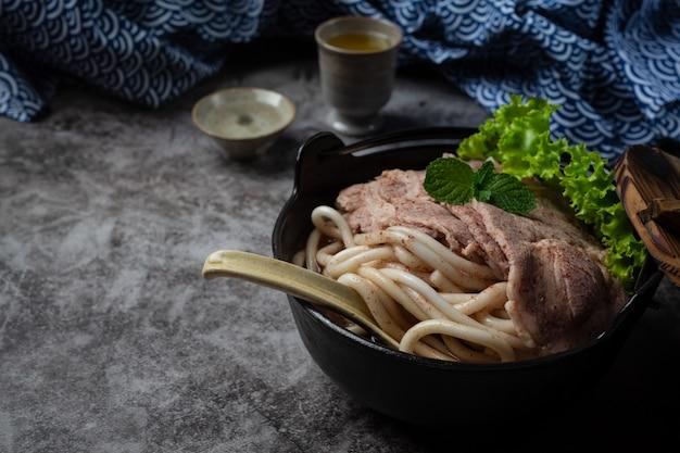 Азиатский стиль суп с лапшой, свининой и зеленым луком тесно в миску на столе.