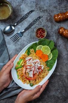 Вкусные морепродукты жареный рис с креветками, яйцом и зеленым луком с супом.