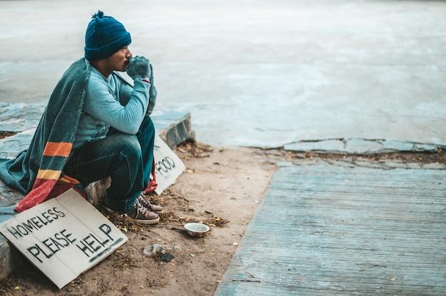 ホームレスで乞食に座る男がメッセージを助けてください。