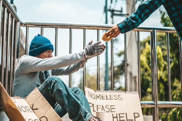 高架に物乞いに座っている男。